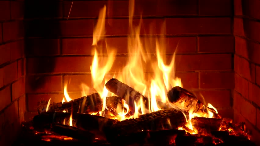 Glorious satisfying close up view on wood burning slowly with orange fire flame in cozy brickwork fireplace atmosphere