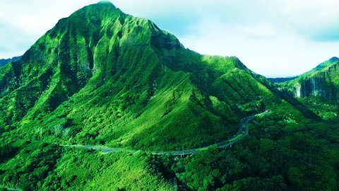 Aerial: Lush Green Tropical Hawaiian Mountain beside Pali Highway.  Vivid Sexy freeway pali cliffs, blue skies, clouds, and cars driving on road.  Colorful KoOlau Mountains Oahu island in Hawaii.