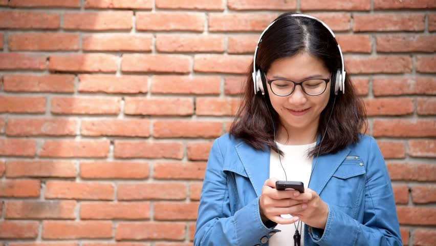 Happy Beautiful Asian woman in blue shirt listening to the music with headphone  via her smart phone on old red brick wall background. copy space. | Shutterstock HD Video #31793698