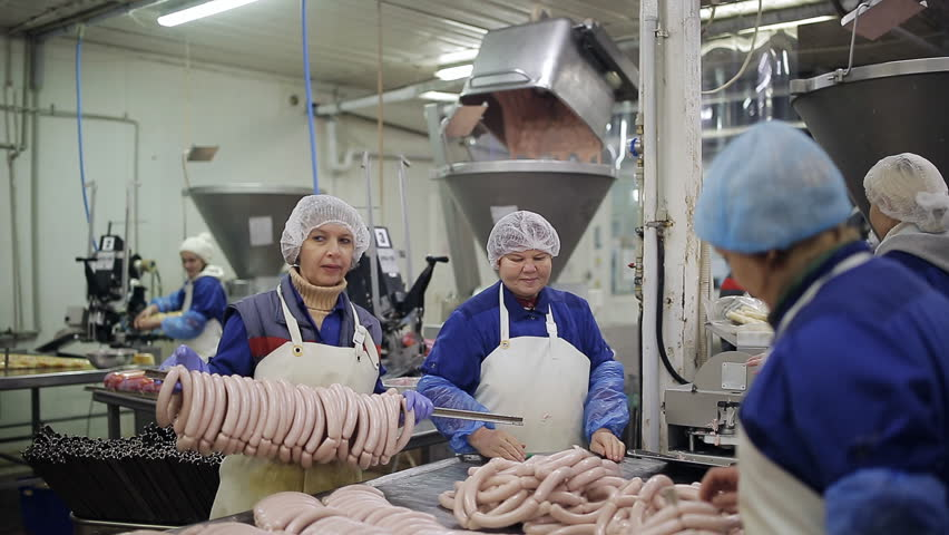 Packing Plant Produce : Workers of the meat packing plant produce sausages stock
