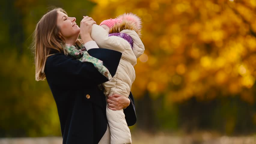 In autumn, when yellow leaves around mom and girl playing with maple leaves, laughing and smiling. Mom hugs and plays with my daughter in the fall. Bokeh and sunlight. | Shutterstock HD Video #31822978