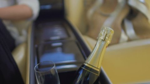 Champagne bottle and glass in inside car storage box, woman sitting at back seat