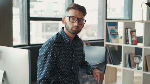 Handsome young man with glasses and beard siting on the table in office, looking on the camera, removes glasses, businessman, designer, programmer. Shot on RED EPIC camera. Slow Motion Shot.