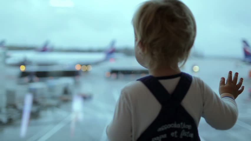 A little boy looks at the planes at the airport. Shallow dof, blinking lights.