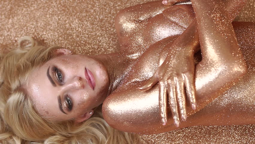 Beautiful girl with gold glitter on her face and body. Beauty fashion model girl with Golden makeup and hair. Sexy Golden girl looking at the camera.