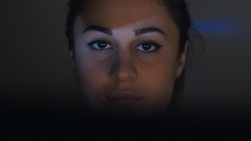 Close-up of a young woman watching a video or film on TV or a computer monitor. Reflection on her face | Shutterstock HD Video #31862908