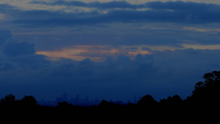 Sunrise over London. Time lapse of London at dawn filmed from Richmond Park. Dramatic clouds silhouette the skyline.
