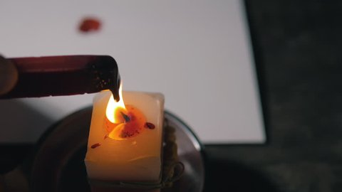 Making wax seal for invitation, melting on candle