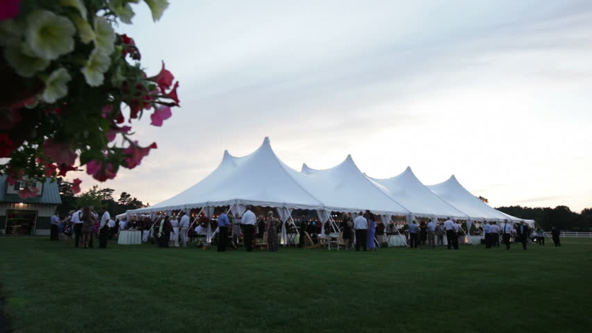 A tent hosting a wedding reception with flowers in foreground