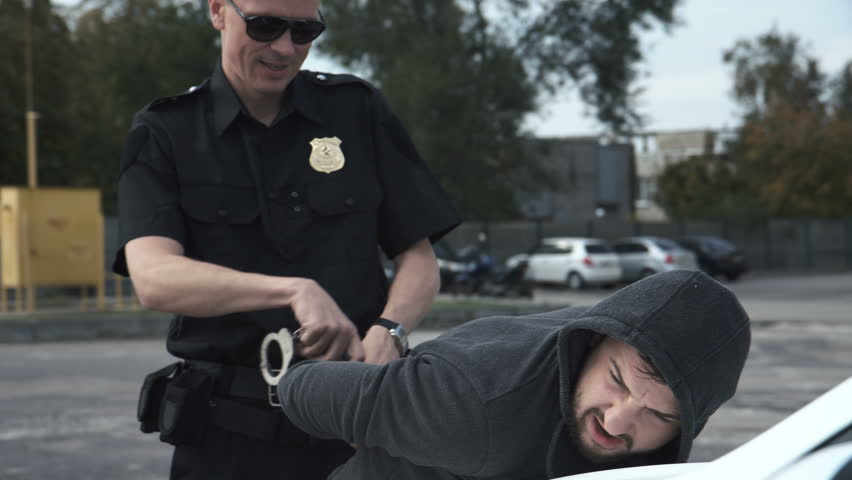 Police officer arresting criminal, putting him on car trunk and reading Miranda rights for him.