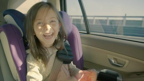 Cute little girl riding in the car at back seat and looking happy.