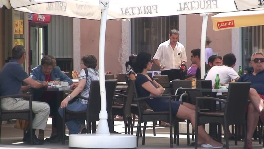 PIRAN, SLOVENIA - CIRCA 2011: People enjoy the outdoors on a cafe terrace.
