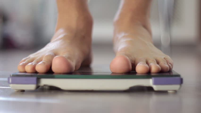 Man measuring weight on health scale