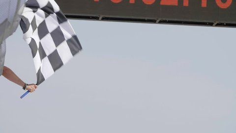 Man holding and waving Checkered race flag in slow motion at finish line on a raceway.