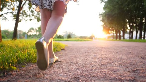 Slender legs of young woman, walking along gravel path in city park, slow motion follow camera. Beautiful evening sun light, bright shine ahead. Grass on left and some trees beside alley