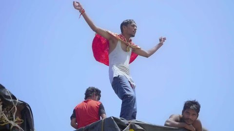 A young Indian man celebrates the Ganesh Chaturthi festival on top of a truck wearing a religious shawl as a cape at Juhu beach, Mumbai