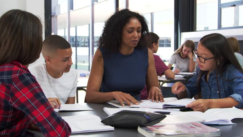 Teacher studying school books in class with high school kids | Shutterstock HD Video #31947418