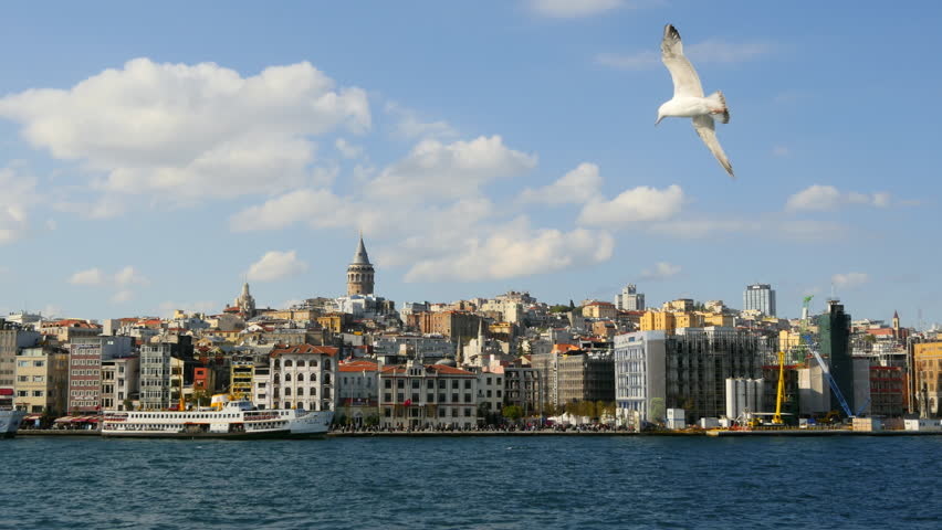 Panning Slow Motion of Istanbul Harbor in front of Galata Tower. City Sea Lines provide a welcome break from the bustle. Gyro stabilized panoramic shot from the waterside