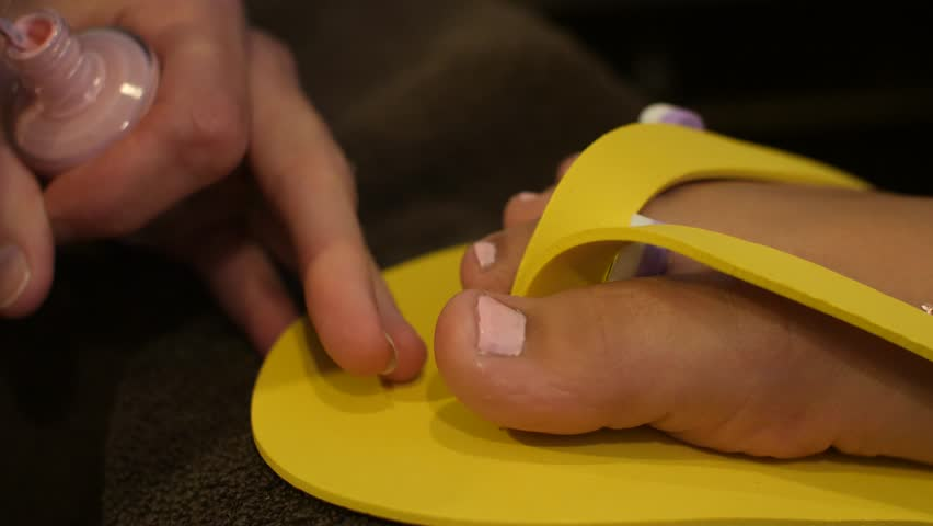 A woman with dark hair making paper crafts a giant yellow flower girl legs doing pedicure polish pedicures children salon spa nails and feet 4k stock mightylinksfo Image collections