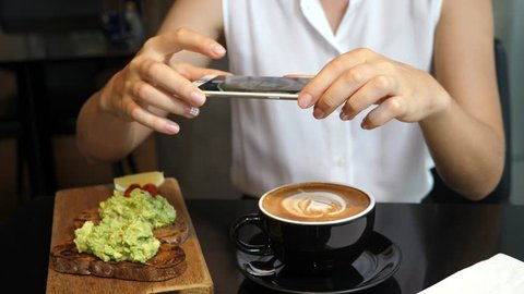 Woman Hands Taking Picture Of Coffee And Avocado Toast With Smartphone. Closeup. 4K.