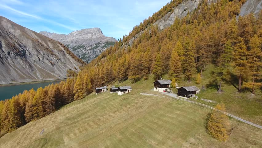 Autumn landscape, little village in a forest with chalet and rural huts. Livigno - Valtellina