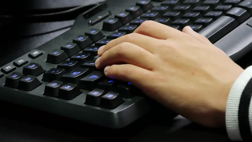 Man hands playing on a gaming computer keyboard. Keyboard with green-blue light. Neon light. | Shutterstock HD Video #32010088