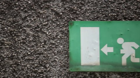emergency exit sign, rusty signboard of person going out of the door (panning shot)