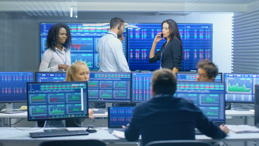 Multi-Ethnic Team of Traders is Busy Working, Talking and Giving Commands to Each Other at the Stock Exchange Office. Dealers and Brokers Buy and Sell Stocks on the Market.Shot on RED EPIC-W 8K Camera