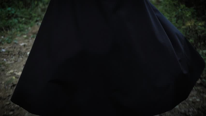 A woman in a long black cloak with a hood is walking along the park, the lady is walking with her back to us, we do not see her face | Shutterstock HD Video #32042698