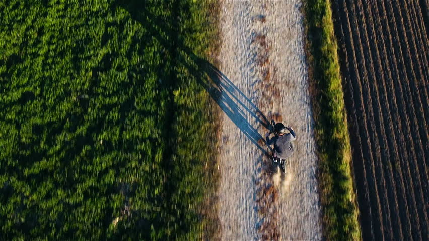 Person bicycling between farm fields aerial top view 4K. Drone flying above single person in focus tracking while riding on gravel road. Big shadow on ground. | Shutterstock HD Video #32055928