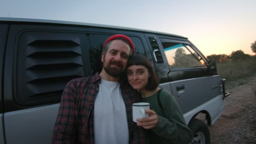 Cute hipster couple of young millennials make video or photo selfie during trip in camping caravan or van, stand in front of car, drink tea and laugh, emjoy youth and life in nature