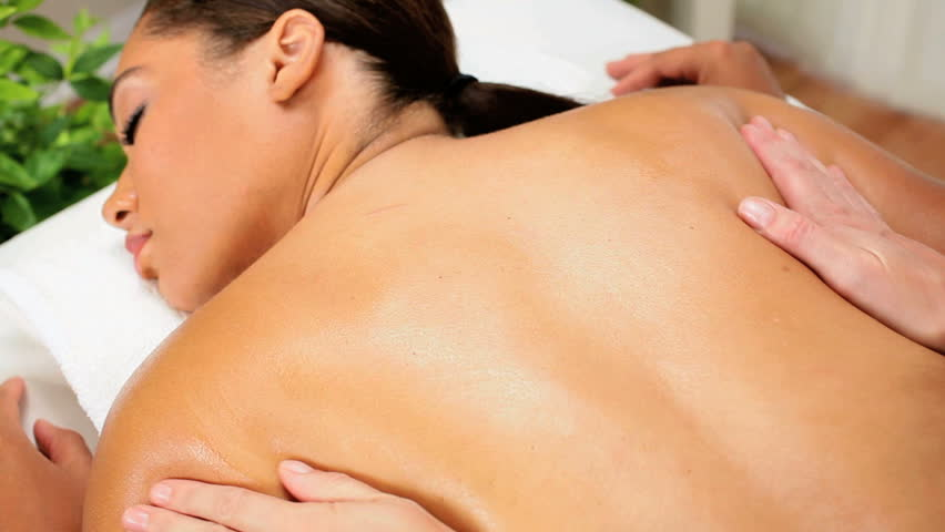 African American female enjoying massage therapy at a luxury health spa