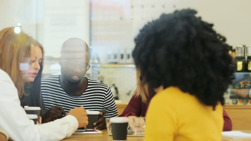 Close up window view of a young diverse group of groupmates discussing different issues while drinking coffee in the restaurant | Shutterstock HD Video #32123638