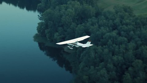 Aircraft flies over the forest and the river