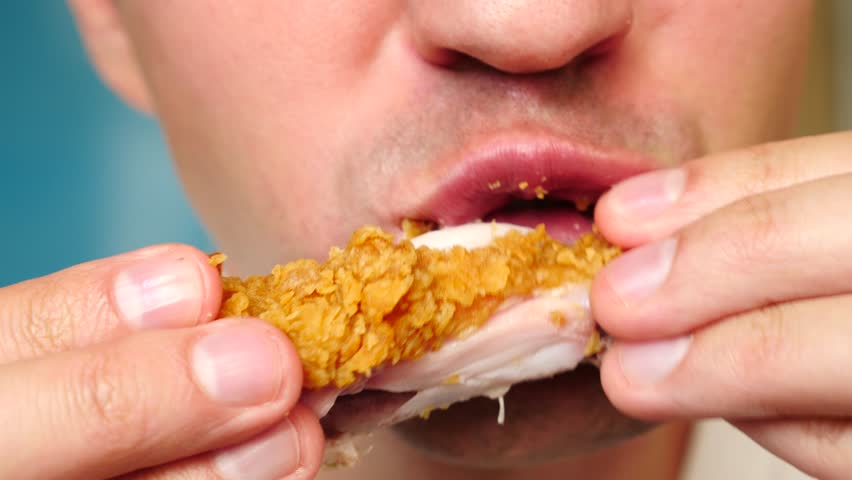 close-up, man eats, fast food, chicken nuggets, wings and french fries.