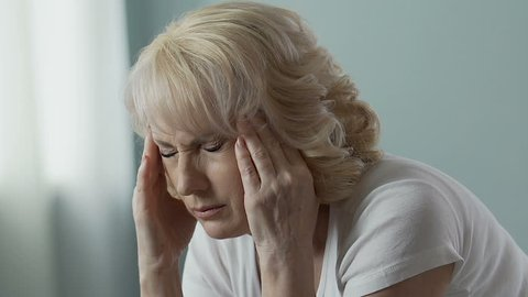 Aged woman rubbing temples intensely, splitting headache, problems with health