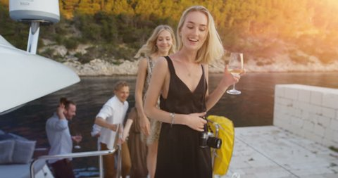 Company of Young Girls and Boys in Fashionable Clothes Leave Yacht To Party. Beautiful Seaside View and Happy People. Shot on RED Epic 4K UHD Camera.