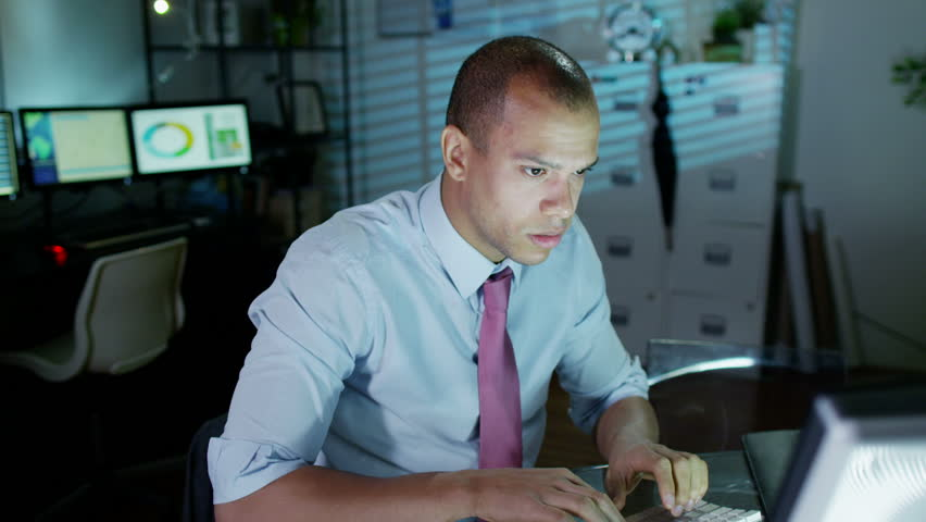 A young professional male is working late at night, a bank of computer screens can be seen in the background. He looks tired and uncomfortable and he loosens his tie