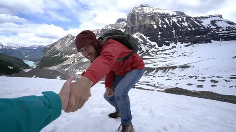A helping hand from teammate on top of the mountain. Partner outstretches arm to reach the one of hiker going up to help him out. People exploration adventure concept