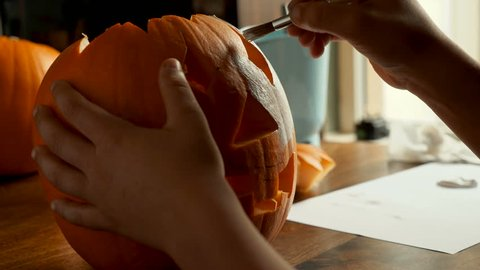 Young boy painting a pumpkin for Halloween on a table