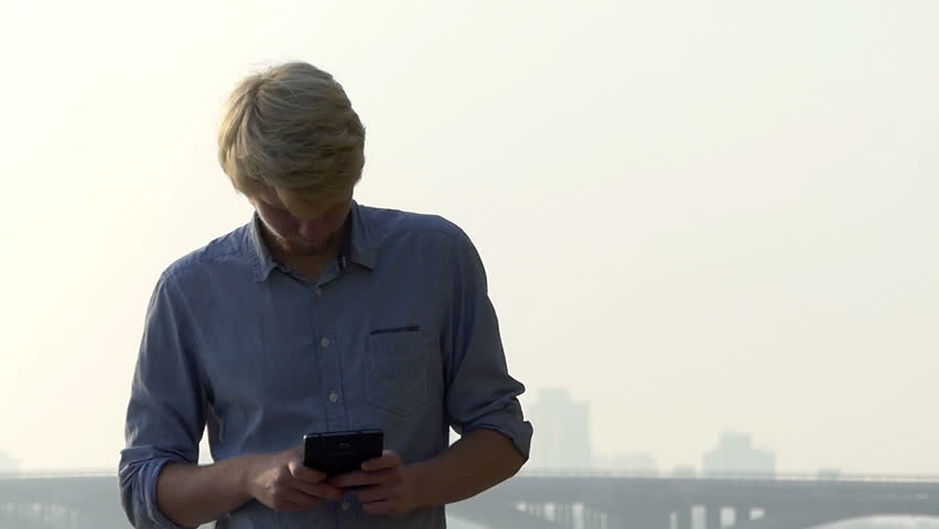 A Thoughtful Young Man Looks At His Smartphone In Summer In Slo Mo. He