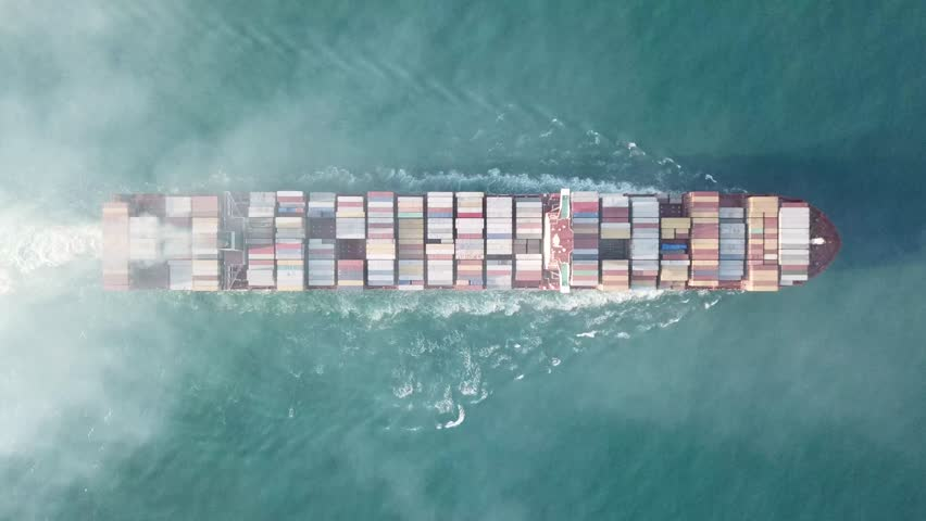 Early morning aerial top-down view of Mega large ULCV container ship sails on open water fully loaded with containers and cargo - 366m long 145K ton - smoke is coming from the chimney