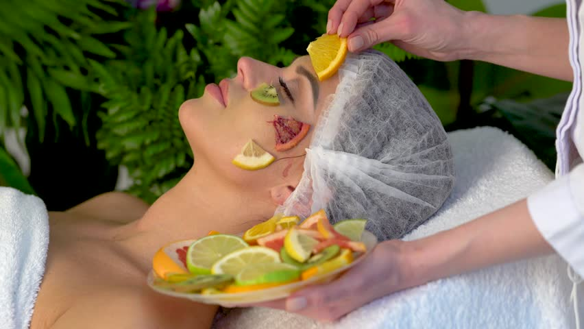 Facial mask from fruits for woman. Skin care with fruit on face in spa salon. Beautician apply slices of avocado, grapefruit and kiwi profile girl in medical hat lying on spa bed for procedure.
