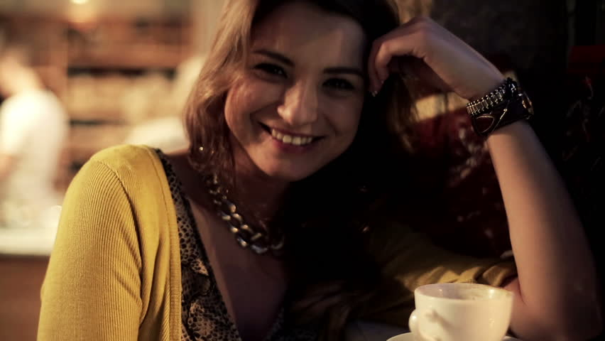 Young attractive woman smiling to camera in cafe, steadicam shot