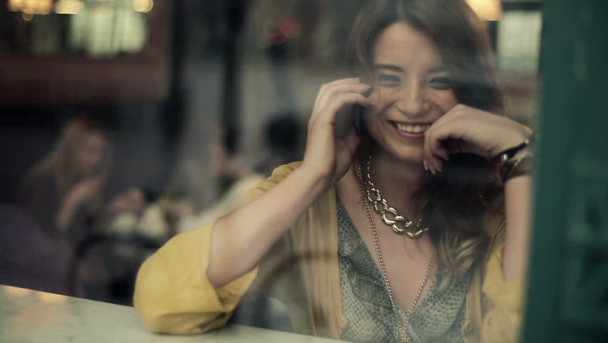 Beautiful woman talking on cellphone in cafe, steadicam shot