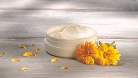 Beautiful women applying marigold cream from jar. Natural cosmetics. Outdoors, summer, nature, organic cosmetics concept.