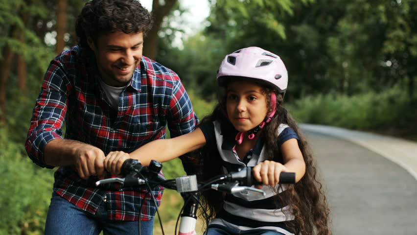 Closeup. Portrait of a little girl and her father. Dad teaching his daughter to ride a bike. Lets her go. Moving camera. Blurred background