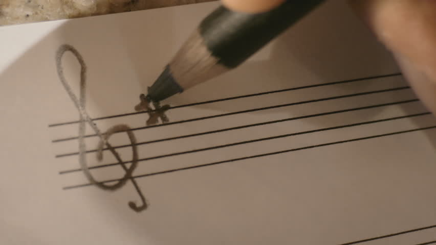 Person hand writing music notes on paper- A G clef in the key of A (three sharps) with a single A note is written, this is abstract and could never be classified in any way as intellectual property.