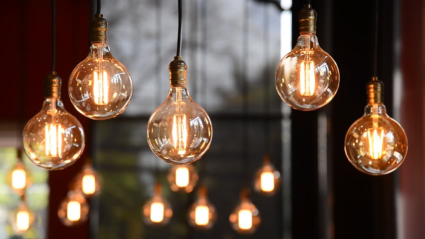 Decorative antique edison style filament light bulbs hanging on ceiling, lamp decoration in shop, electric light, incandescent lamp, hot spiral of tungsten bulb.