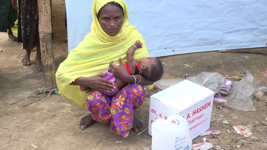 TEKNAF, BANGLADESH - OCTOBER 25, 2017: A Rohingya Refugee from Myanmar just arrived in Bangladesh with her son and a few belongings